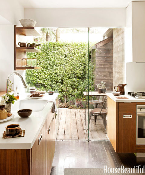 "In Mark Egerstrom's 1,200-square-foot West Hollywood home, the wood floors of the kitchen extend out to a coordinated deck through glass shower doors, creating the illusion of a much bigger space. The walnut cabinetry was designed by Egerstrom: ""It's my take on old farmhouse kitchens, updated to the 21st century."" It was fabricated by Gary Ferguson of Case and Grain with Glacier White Corian counters and custom inset handles.<br /><br /><br /><br />"
