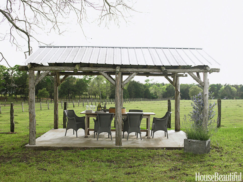 A rustic gazebo is the farm's only real dining room. Janus et Cie's indoor-outdoor Cannes wicker chairs surround an antique pine table that Barber stained gray to blend with the weathered posts.