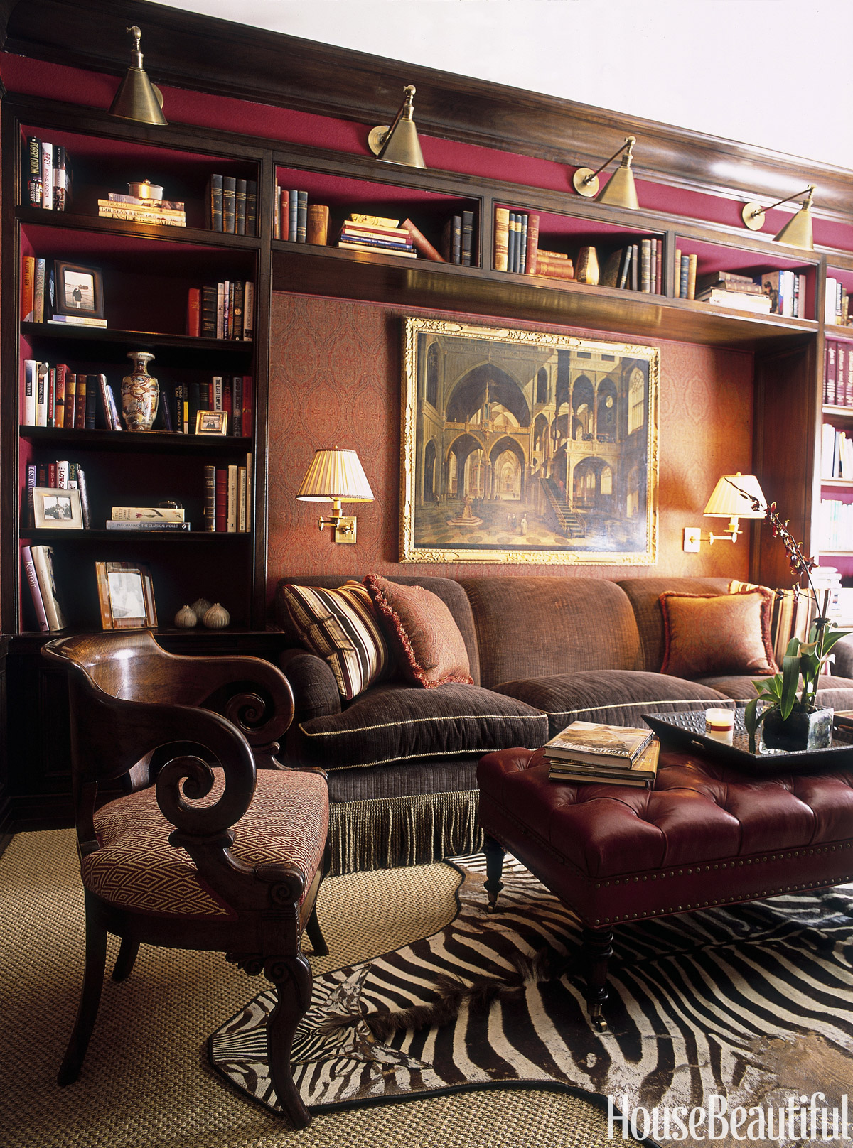 """Red libraries are best!"" says designer Alessandra Branca. Walls are upholstered in wool paisley. The sofa and ottoman are Branca designs."