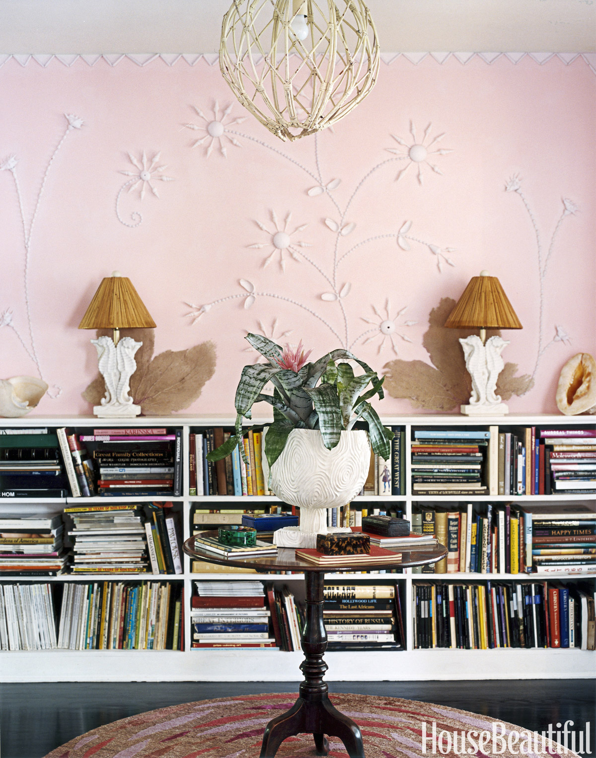 Designed by Gene Meyer and Frank de Biasi, this library features seahorses throughout the room, including the vintage plaster lamps with rattan shades. The pink on the walls, decorated with seashells, is a custom mix that is fitting for this Miami home.