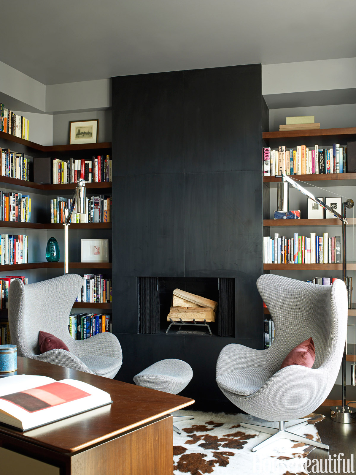 """The attitude of the library is modern, but it's cozy and warm — almost womblike,"" architect David Mann says of this space in a New York City apartment. Walls are painted Ralph Lauren Orion Grey. Mix Table lamp from Luceplan."