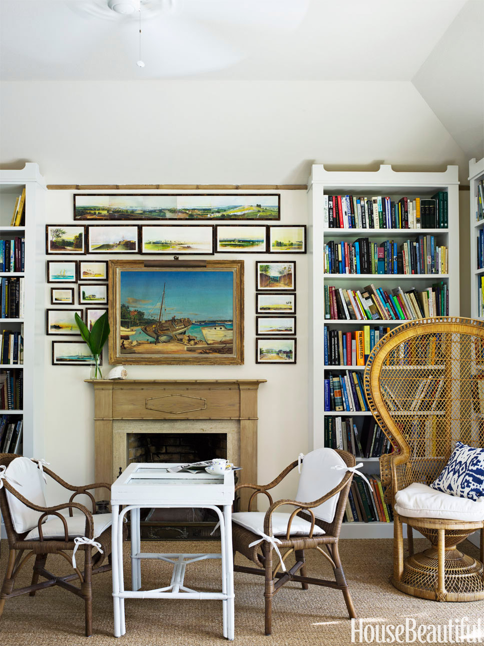 Crowning the library hearth in Amanda Lindroth's Bahamas house are 19th-century watercolors of the Bahamas by Gaspard Le Marchant Tupper. Willow Group rattan chairs are pulled up to a backgammon table.