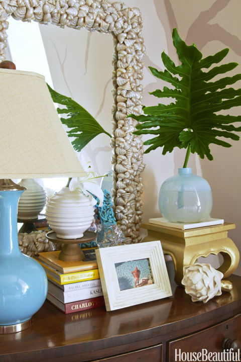A shell-encrusted antique mirror brings a note of pearly luster to the room.