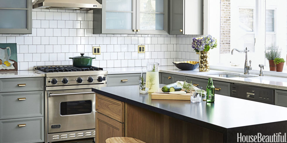 "Designer SuzAnn Kletzien transformed this Chicago kitchen with new fixtures and mixed metals, unifying the space with gray and white, as seen in the backsplash — plus hints of brass.  She swapped in an island for the existing peninsula, but the appliances stayed put. ""That way we could afford to splurge on a wine refrigerator,"" says Kletzien."