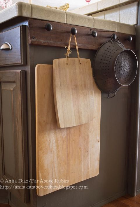 Heavy, clunky kitchen tools, like cutting boards and colanders, fit awkwardly into cabinets — so why not hang 'em on the outside instead? This way they'll be easy to grab and put away.<br />See more at Far Above Rubies »<br />