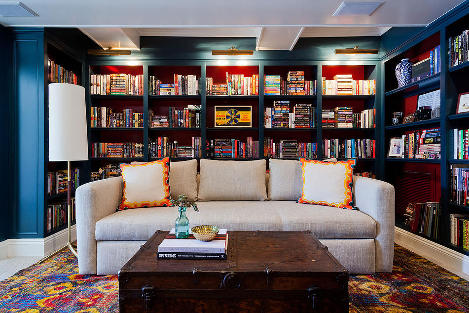 Quando usado corretamente, um matiz profundo pode melhorar as características arquitetônicas. Nesta sala de estar / biblioteca, um azul dramático contrasta os painéis traseiros vermelhos da estante embutida. Esta rica justaposição dá a dimensão da sala, criando profundidade que faz com que a sala se sinta um pouco maior - ainda mais íntimo.