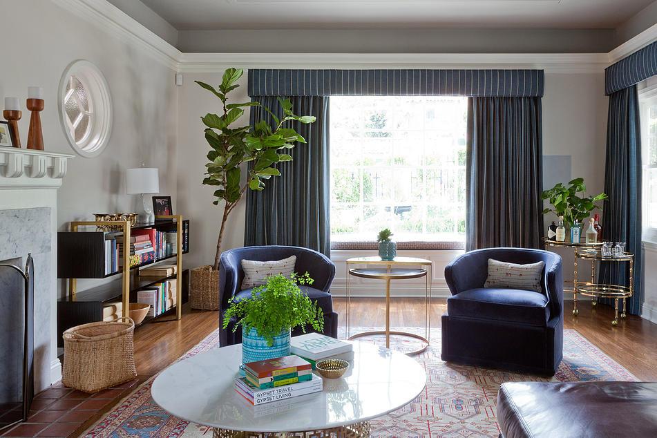Uma janela nua não faz nada para fazer um quarto se sentir maior ou mais elegante. Tailored tratamentos de janela, se pendurado perto do teto (ou moldagem, como nesta sala de estar), faz uma janela parece maior.
