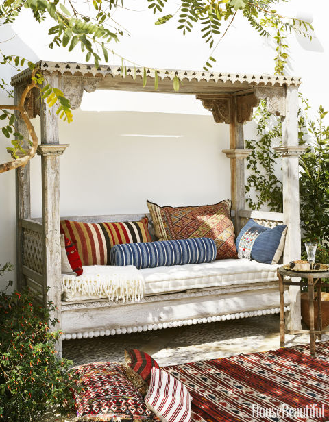 Vintage textiles enliven an Indonesian daybed outside a Richmond, Virginia, home.