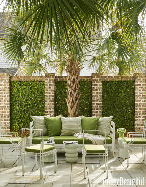 In the interior courtyard, fig ivy softens a brick wall and a mature palmetto tree adds a sense of permanence to a brand-new South Carolina house. The West Elm sofa is covered in a Sunbrella fabric.
