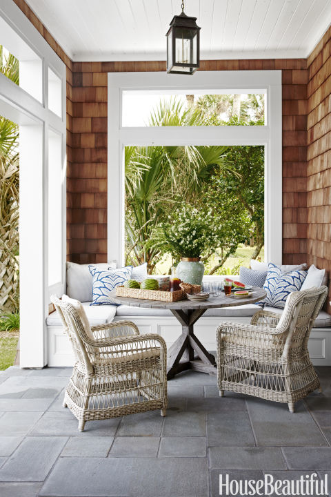 A banquette accommodates lunch al fresco at a Florida home. Designer Andrew Howard sourced the wicker armchairs and teak table from Kingsley-Bate.
