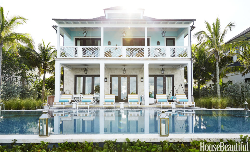 "Marshall Watson and Kate Reid embellished the rear facade of a Bahamian retreat with Bevolo gas lanterns. For the pool's glass mosaic, ""we spent hours trying to match the rich turquoise blue of the ocean,"" Watson says. ""It's a definite resort feeling. You know you've arrived."" The pool perimeter is trimmed in coral stone."