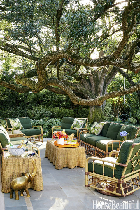 Pieces from Celerie Kemble's Lane Venture collection furnish the flagstone patio outside of Bailey McCarthy's Texas home. An 80-year-old oak provides plenty of shade.