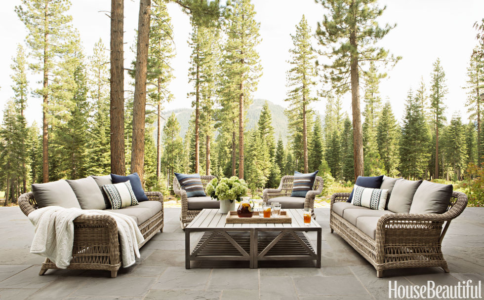 "Matt O'Dorisio created an elevated outdoor patio for a Lake Tahoe vacation home. The seating area combines contemporary teak with more traditional wicker. ""It's like an extension of the living room into the forest,"" he says."