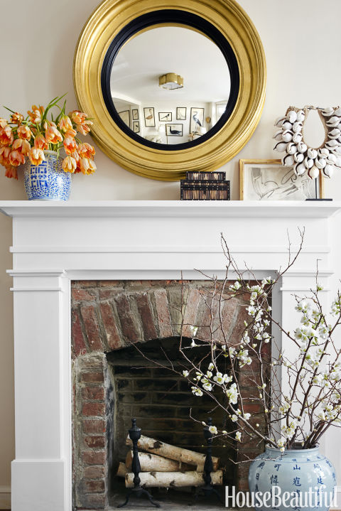 A bull's eye mirror by Carvers' Guild surveys the living room from above a custom mantel painted in Benjamin Moore's White Dove.