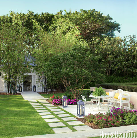 A dining pavilion flanked with flowers anchors the backyard of a Florida home.<br />