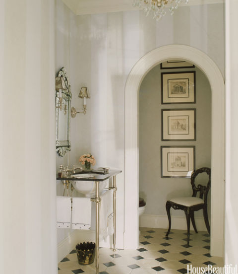 A glimpse of an inner space — like the arched alcove that designer Anne Miller provides here — makes a powder room feel larger.