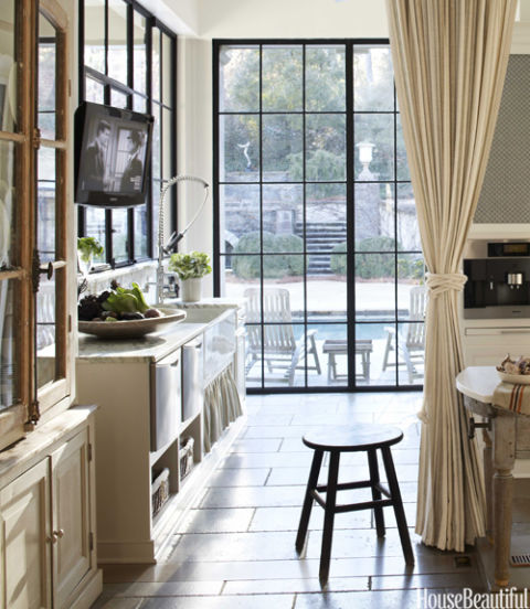 "In the kitchen of the same Atlanta house, a linen curtain runs on a track spanning the room and can be pulled ""to conceal the mess of preparation,"" Webb says. Steel-and-glass casements frame views of the pool and garden. KWC Gastro faucet."