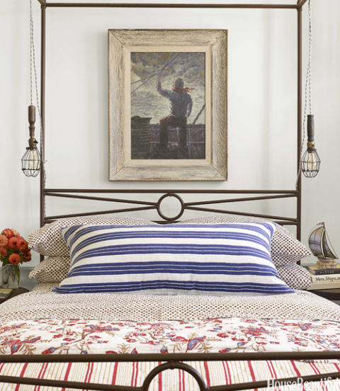 """We call this 'the sailor room,' because we went all out with the nautical theme,"" designer Ken Fulk says of a bedroom in his Massachusetts vacation house. ""The mix-and-match nature of the patterns and faded batik prints make it feel like it's a collection of old textiles brought back from a journey at sea."" John Robshaw bedding. Antique cage lights hang from an antique metal four-poster bed that belonged to the previous owner."