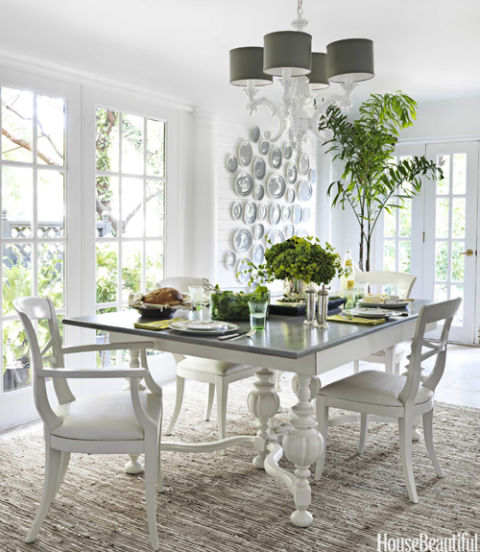 "This Kansas City house's dining room, a former loggia, is ""light, bright, and airy,"" homeowner and designer Zim Loy says. ""I accomplished that with lots of white paint."" She bought a beat-up old $60 table at an estate sale and gave it a fresh new look by the painting the base high-gloss white. Its curves echo the arms of the Barbara Cosgrove chandelier."