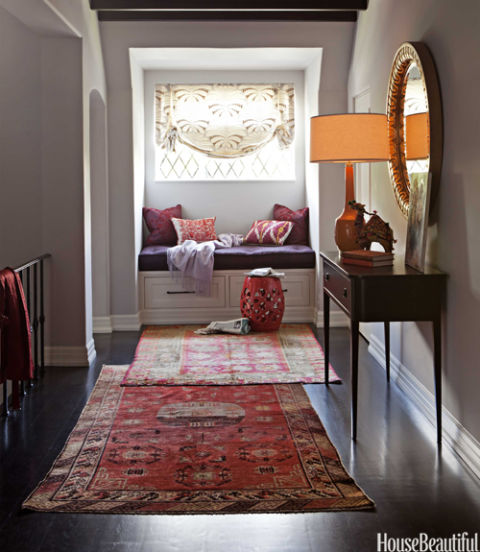 "In the second-floor hallway of a California house, designer Betsy Burnham overlaps Turkish runners from Rugs & Art, drawing the eye to a Moroccan-inspired reading nook. The vintage carpets ""can transform a plain hallway into a decorated space,"" Burnham says. ""A really faded, tattered rug is instantly Bohemian."" The window seat is covered in Tibet woven silk from S. Harris. Pillows by Hollywood at Home; garden stool from Rolling Greens."