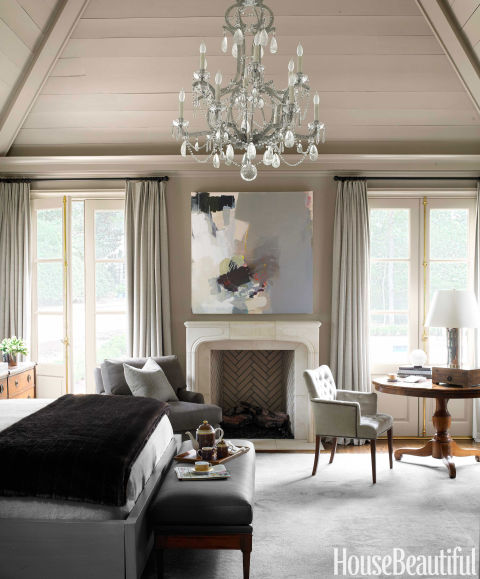 "Ceiling, walls, and trim are all painted the same color — Benjamin Moore's Berkshire Beige — to create a serene backdrop in the master bedroom. Curtains in Threads' Hush melt into walls. Designer Robert Brown says he chose the Oushak rug from Keivan Woven Arts because it ""feels as warm as an old blanket,"" and he picked David Iatesta's Marseille chandelier ""for romance."""
