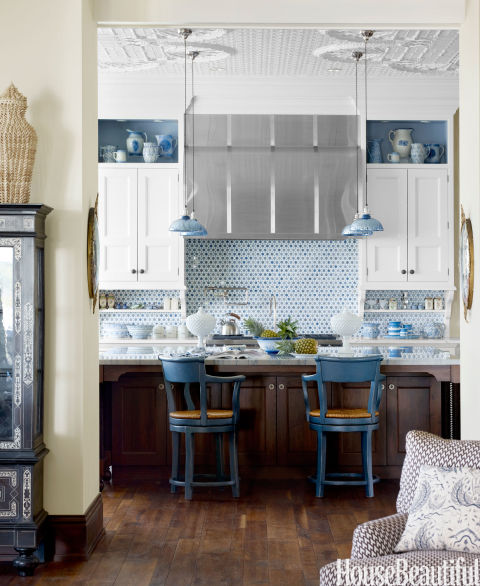 The kitchen backsplash, from Urban Archaeology, is beautiful and practical, and open shelves for display break up the cabinetry in this Lake Michigan home's kitchen. Designer Martin Horner chose blue mercury-glass pendants from Gallery L7 to pick up the color theme and the home's exotic style.
