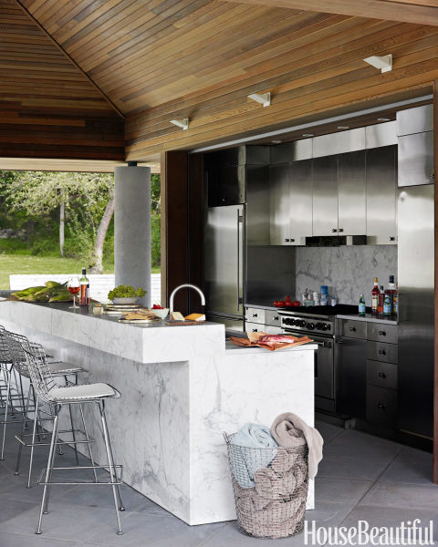 In designer Bonnie Edelman's Connecticut house, the pool kitchen's stained oak ceiling pours warmth over cool stainless-steel cabinets. A drop-down metal gate protects appliances from rain.