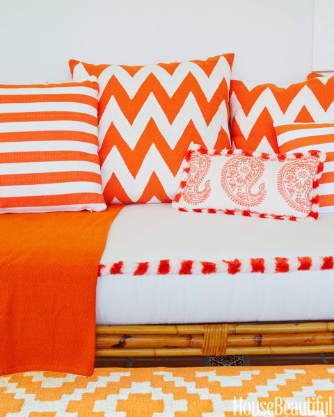 Pillows in Pine Cone Hill fabrics wake up a veranda daybed.