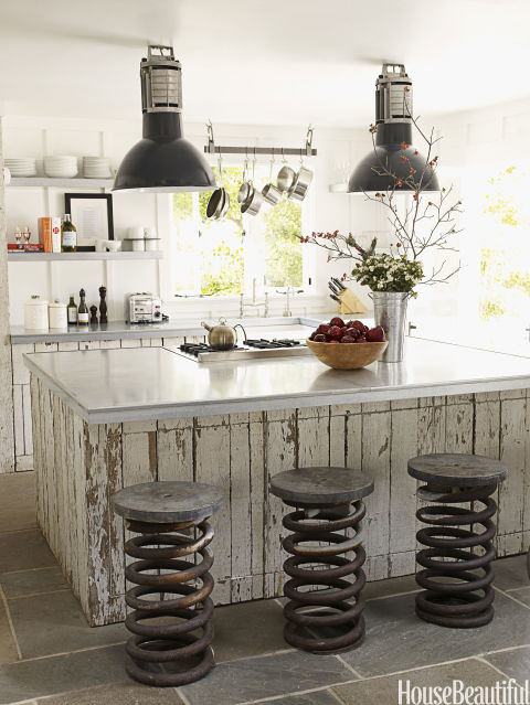 Open shelves, instead of upper cabinets, give a small kitchen in designer Ken Fulk's Napa Valley house an airy feel. The shelves and countertops are made of galvanized metal and the cabinetry is made from old fencing. Vintage truck springs, used as stools, were found at Artefact Design & Salvage. Fulk spotted the vintage industrial pendant lights at the Paris flea market.<br />