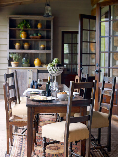 mix and match antique chairs surround a rustic dining table on the