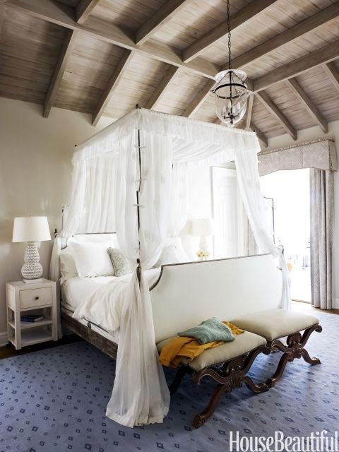 """Você realmente se sente como se estivesse flutuando sobre uma nuvem nesta cama.  Em uma casa de praia Geórgia, altura de dossel da cama do quarto principal campanha de estilo sobe em direção ao teto de carvalho angustiado e dá escala para o quarto.  """"A maioria das pessoas adoram uma cama de dossel, e dormindo debaixo de toda aquela voile branco é um sonho"""", diz o designer Jim Howard."""