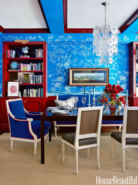 In a New York apartment, de Gournay's hand-painted cobalt-blue Earlham wallpaper makes a big impression in the dining room. Yet, the crisp white and apple red decor hold their own against this electric hue, balancing the bold look.