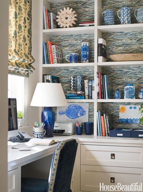 'Galhos Faisão wallpaper energiza a vasta extensão de prateleiras no escritório em casa da esposa de uma casa em Houston, Texas.  As máscaras romanas são Flor indiana de Jasper.  Designer Ann Lobo usado borda do tecido para aparar a cadeira.