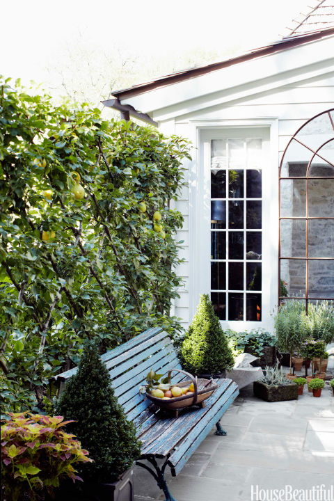 A Southern-inspired secret garden is enclosed by pear trees espaliered on a trellis.<br />