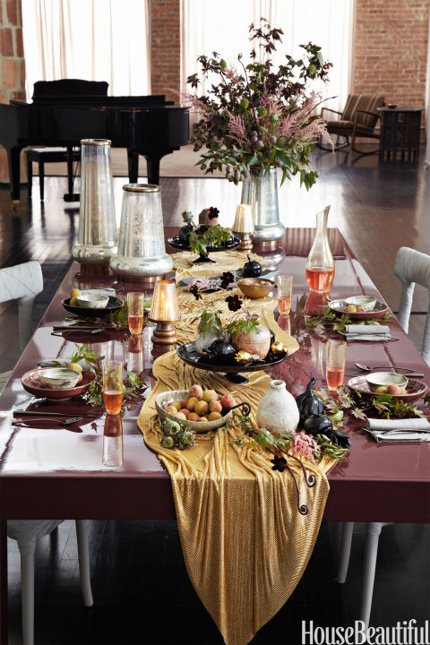 """Add shimmer to your fall tablescape. Designer Laura Kirar sets a glossy table for a dinner party. """"I kept high objects on one end and draped the gold mesh runner down the center, creating the effect of a waterfall,"""" she says. Shop a similar look:yellow table runner ($23, amazon.com), black cake stand ($67, amazon.com), red bowls ($76, jossandmain.com)"""
