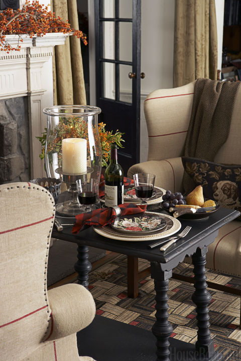 """Ralph Lauren brings his classic all-American style to a supper for two near the fireplace. """"Dining doesn't have to be confined to the dining room or kitchen,"""" he says. """"A fireside meal is intimate and inviting."""" Shop a similar look:black and red napkins ($12, amazon.com), hurricane candle holder ($29, target.com), floral place setting ($111, amazon.com)"""
