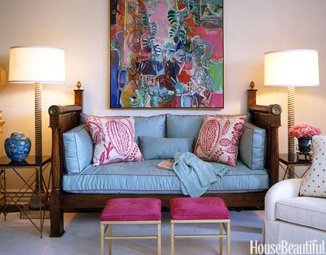 In Courtney Haas's living room, an antique mahogany daybed is flanked by a pair of floor lamps from Downtown. Throw pillows covered in Pali from Manuel Canovas. Painting over daybed by Robert Frame.