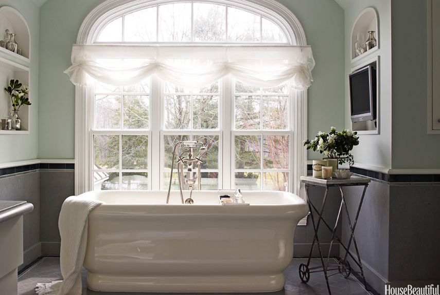 Light Green Master Bath With Freestanding Tub Next To Large Window