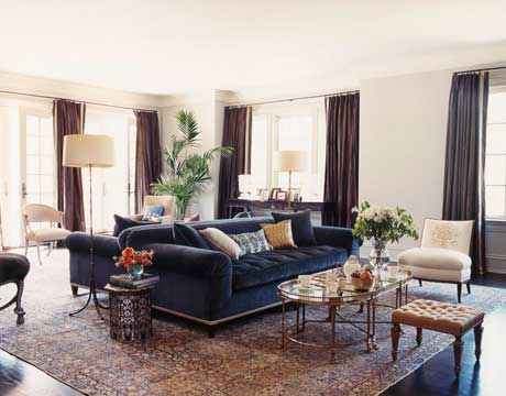 "Back-to-back sofas define intimate seating areas in the vast living room. They're upholstered in a Classic Cloth velvet, Marlowe in India Ink, that has ""an iridescent quality,"" Nahem says. ""The color changes depending on the light. One day it's gray, another day it's blue."" A 1940s Robsjohn-Gibbings slipper chair is updated with boldly embroidered Carma from Bergamo. Walls are painted Farrow & Ball's Elephant's Breath."