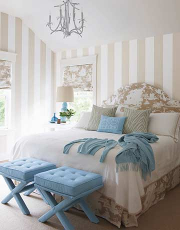 """The printed fabric in the guest bedroom is whimsical,"" Braff says, ""but the beige and aqua palette is very restful."" Bed and curtain fabric is Lyford Background in Inca Gold on White, by China Seas. Wallpaper is Millennium Stripe in Beige and White, by First Editions. Ottomans are by Jonathan Adler."