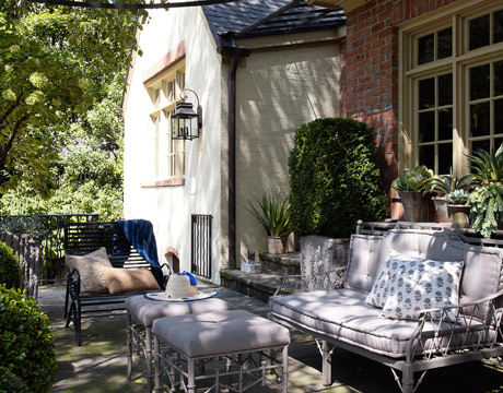 The outdoor sofa and ottomans were painted gray and upholstered in taupe Sunbrella to harmonize with the stone terrace.