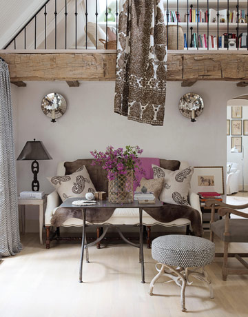 "A Moroccan tapestry hangs from the living room loft, between mirrored sconces that are ""like earrings for the wall,"" Brinson says. She constantly changes the look of the seating area with different textiles, pillows, and lampshades. The antique French industrial table is one of a pair — the other one is in the entry. Pillows from Two Girls in Avignon."