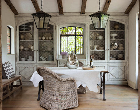 "The dining room has a soothing, dreamy aura. ""I can't stand faux anything,"" says Brinson, ""but I love the cabinets — I did three layers of white mixed with gray, and a spray-on lacquer finish. And I love seeing dishes through the chicken wire."" Wicker chairs and white cowhide soften the industrial edge of the table, which extends another three feet: ""If we have a dinner party, we just whisk the bench over and grab some of those weird little stools we have around."" A Moroccan necklace drapes a bottle from BoBo Intriguing Objects."