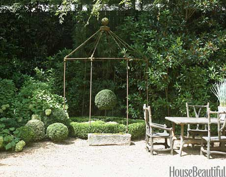 "A stone faux-bois dining table from France and iron gazebo from Anthropologie sit at the end of designer Jill Sharp Brinson's gravel driveway. ""The gazebo was a display at a mall store in Atlanta, and I lusted after it for years. One day I was there shopping and I saw a 'for sale' tag on it. I bought it on the spot."" With the help of Dan Cleveland of Boxwoods Gardens and Gifts, Brinson planted waves of clipped boxwood, magnolia, hydrangea, anise, and holly to screen out the 20-story building just 15 feet away."