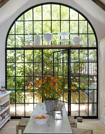 "Brinson replaced a tile top on the Martha Stewart table with Georgia marble: ""Honed white marble makes it look like it's salvaged from some great patisserie in France. At least I can pretend. But the showstopper in my kitchen is the 14-foot-high arched steel window and door. The drama is big in here."""
