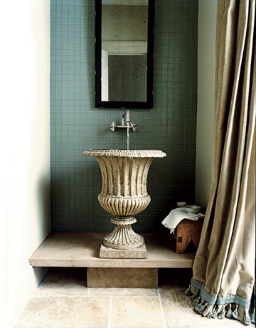 This iron garden ornament was brought indoors by designers Bobby McAlpine and Susan Ferrier. A stone platform raises the urn's inset basin to conventional sink height.