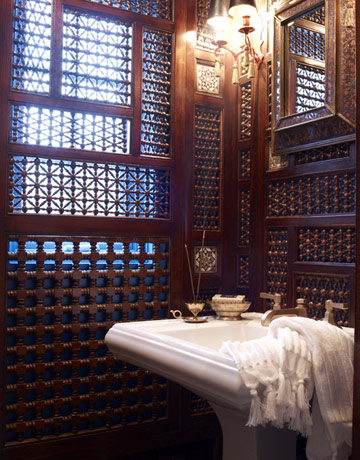 Designer Laura Kirar adapted antique Moroccan fretwork panels to transform a dark leftover space below a stairway into an alluring Orientalist jewel box.