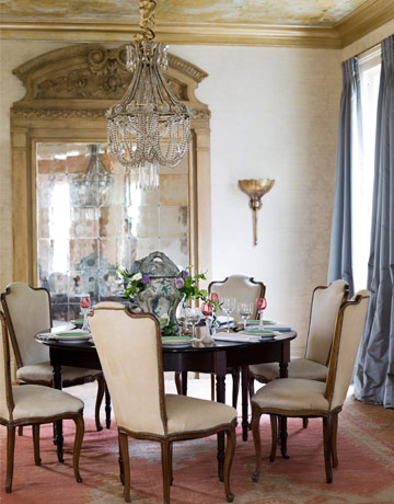 formal dining room with crystal chandelier and large mirror and pink carpet - House Beautiful Dining Rooms
