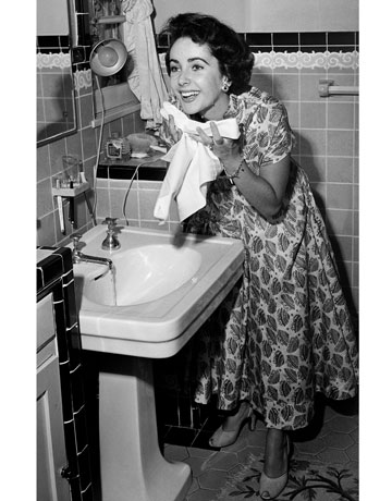 her face at a pedestal sink in a classic  midcentury-style bathroom