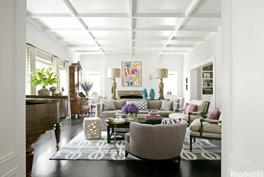 """Float furniture away from the walls: It creates more intimate seating,"" designer Betsy Burnham says. She did just that in the living room of this California house. The console table separating back-to-back sofas is decked with vintage goddess figurine lamps and Chinese monkeys ""for a Tony Duquette, William Haines flavor."" Sellarsbrook rug, the Rug Company. Rectangular Cocktail Table, Baker."
